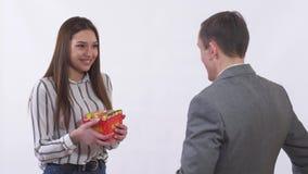 Mannen i dräkt ger en flicka asken med gåva och steg tätt upp Flickaleenden och blygt Unga par för nära övre stående