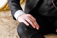 Mannen i dräkt satte hans hand på hans knä arkivbild