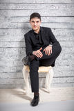 Mannen i dräktsammanträde på stol med ben korsade på studion Royaltyfria Foton