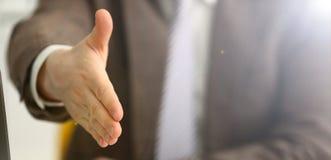 Mannen i dr?kt och bandet ger handen som h?lsningar royaltyfria bilder