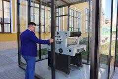 Mannen i en blå dräkt ser tryckpressen bak exponeringsglaset royaltyfri fotografi
