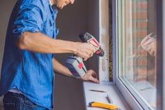 Mannen i en blå skjorta gör fönsterinstallation royaltyfri foto