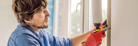 Mannen i en blå skjorta gör fönsterinstallationsBANRET, LÅNGT FORMAT royaltyfria bilder