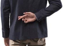 Mannen i en dräkt korsade hans fingrar bak hans baksida Royaltyfri Fotografi
