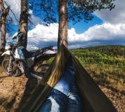 Mannen i en hängmatta på pinjeskogberget, den utomhus- handelsresanden kopplar av, enduroen av vägmotorcykeln royaltyfria foton