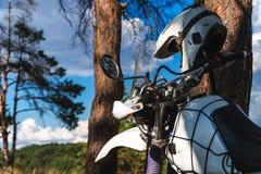 Mannen i en hängmatta på pinjeskogberget, den utomhus- handelsresanden kopplar av, enduroen av vägmotorcykeln arkivbild