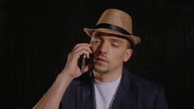 Mannen i en hatt och ett omslag talar på telefonen lager videofilmer