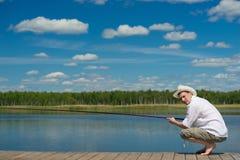 Mannen i en hatt och en vit skjorta, fiskar på sjön royaltyfri foto