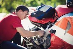 Mannen i en röd T-tröja reparerar en motorcykel royaltyfria foton