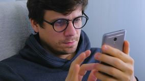 Mannen i exponeringsglas skriver ett meddelande i socialt massmedia på smartphonen Framsida- och telefonnärbild stock video