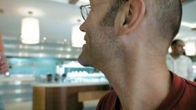 Mannen i exponeringsglas välkomnar hans vän på restaurang arkivfilmer