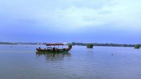 Mannen i fartyg seglar på floden mot Cityscape under blå himmel arkivfilmer
