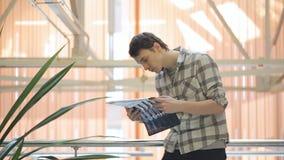Mannen i grå rutig skjorta står i korridor och analyserar försiktigt röntgenstrålar arkivfilmer