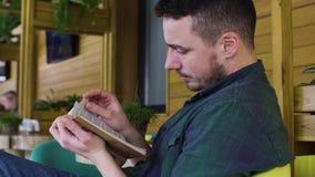 Mannen i grön skjorta läser boken i kafét arkivfilmer