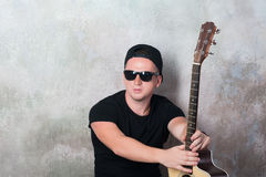 Mannen i grov bomullstvill kortsluter sammanträde bredvid en gitarr på väggbakgrunden i stilgrunge, musik, musikern, hobbyen, liv Royaltyfri Foto