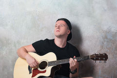 Mannen i grov bomullstvill kortsluter sammanträde bredvid en gitarr på väggbakgrunden i stilgrunge, musik, musikern, hobbyen, liv Arkivbilder