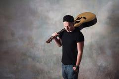Mannen i grov bomullstvill kortsluter stending bredvid en gitarr på väggbakgrunden i stilgrunge, musik, musikern, hobbyen, livsst Fotografering för Bildbyråer