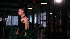 Mannen i gymnastiksalen lyfter skivstången med tungvikten över hans huvud stock video
