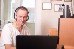 Mannen i hörlurar sitter mellan en bärbar dator och en dator Fotografering för Bildbyråer