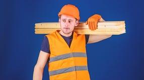 Mannen i hj?lm, h?rd hatt och skyddande handskar rymmer tr?str?len, bl? bakgrund Snickare inredningssnickare, stark byggm?stare royaltyfria bilder