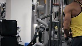 Mannen i idrottshalldrevmusklerna av händer med en kvarterströmkretssimulator lager videofilmer