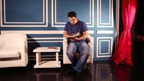 Mannen i jeans sitter nära tabellen i blåttrum och läser boken arkivfilmer