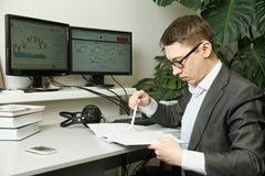 Mannen i kontoret för dator övervakar studierekord i en anteckningsbok Arkivbild