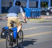 Mannen i kortslutningar och t-skjorta ritter cyklar på stadsgatan med ett försök som trycker på pedalerna arkivbild