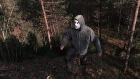 Mannen i läskig allhelgonaaftonmaskering och machetet kliver upp på kullen stock video