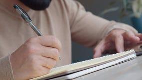 Mannen i ljus tröja skriver i en anteckningsbok med en svart penna, närbild arkivfilmer
