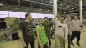 Mannen i lock talar i mikrofon Händer för rullskateboradåkarehaise, leende Konkurrens i skatepark lager videofilmer
