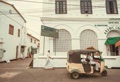 Mannen i muslim klär att gå på gatan med den auto rickshawen som bort kör royaltyfri fotografi