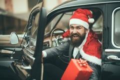 Mannen i röd hatt levererar xmas-gåvor i retro bil arkivfoto