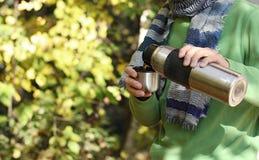 Mannen i randig halsduk häller ett te eller ett kaffe från termoset in i koppen royaltyfri fotografi
