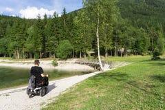 Mannen i rullstol i höstligt parkerar nära sjön royaltyfria bilder