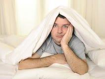 Mannen i säng med ögon öppnade lidandesömnlöshet och arkivbilder