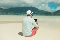 Mannen i sanden med ben korsade läs- ipad Arkivbild