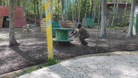 Mannen i skyddande likformig och maskering sitter i bakhåll med vapnet då står söker efter upp till fienden som spelar paintball lager videofilmer
