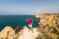 Mannen i slutet av vagga nära Atlantic Ocean talar på telefonen på soliga dagar för sommar Arkivfoto