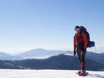 Mannen i snöskor i bergen arkivbilder