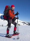 Mannen i snöskor i bergen arkivfoto