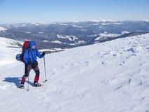 Mannen i snöskor i bergen royaltyfri foto