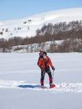 Mannen i snöskor i bergen fotografering för bildbyråer