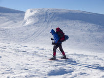 Mannen i snöskor i bergen royaltyfri bild
