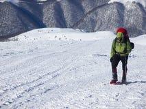 Mannen i snöskor i bergen royaltyfria foton