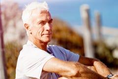 Mannen i sportar bär sammanträde på stranden Arkivbilder