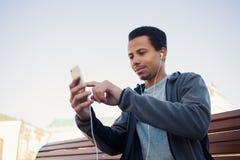 Mannen i sportar likformig och hörlurar lyssnar till musik genom att använda en smartphone arkivbild