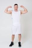 Mannen i sportlikformig visar biceps Royaltyfri Bild