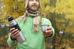Mannen i stucken hatt och halsduk, med leende erbjuder den varma drinken - te eller kaffe från termoset till någon, främre sikt royaltyfria foton