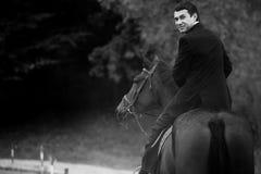 Mannen i svart dräkt vänder, medan han rider en häst Arkivfoton